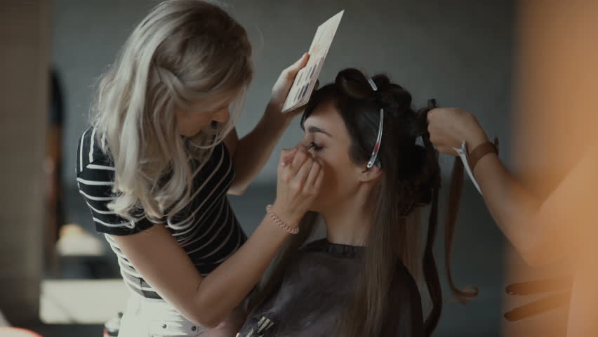 Specialist doing makeup for model. Gentle make-up for the young girl. Showing of models.