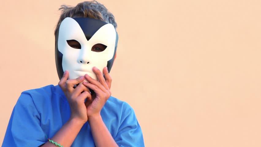 Little boy holds two masks near faces and then removes them one for another