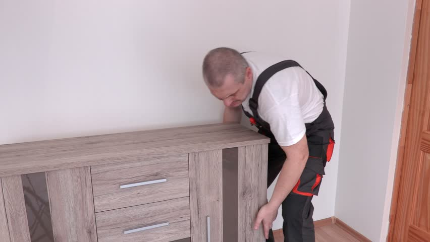 Worker try lifting furniture and get back pain   4K stock video clip. Worker Try Lift Up Furniture Stock Footage Video 25673045