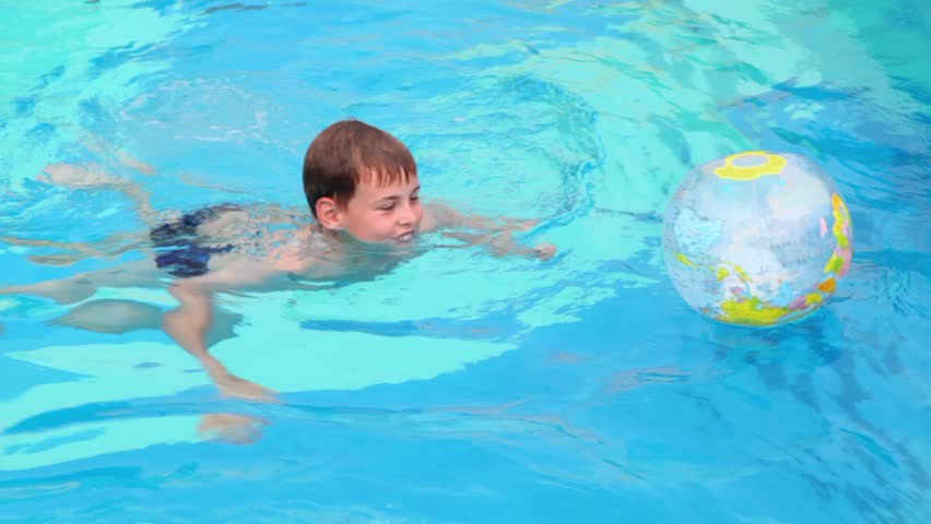 Little boy swims in pool and play with inflated ball | Shutterstock HD Video #2567387