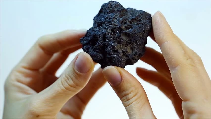 Manganese ore - Manganese (Mn). Mining and Extraction of minerals. Hand Holding Piece of black Manganese ore. Heavy industry