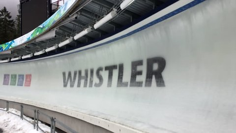Whistler-Blackcomb, British Columbia, Canada -- March 2017. Public bobsled passes in slow motion, 2010 Vancouver Olympic sign in ice at Whistler Sliding Centre.
