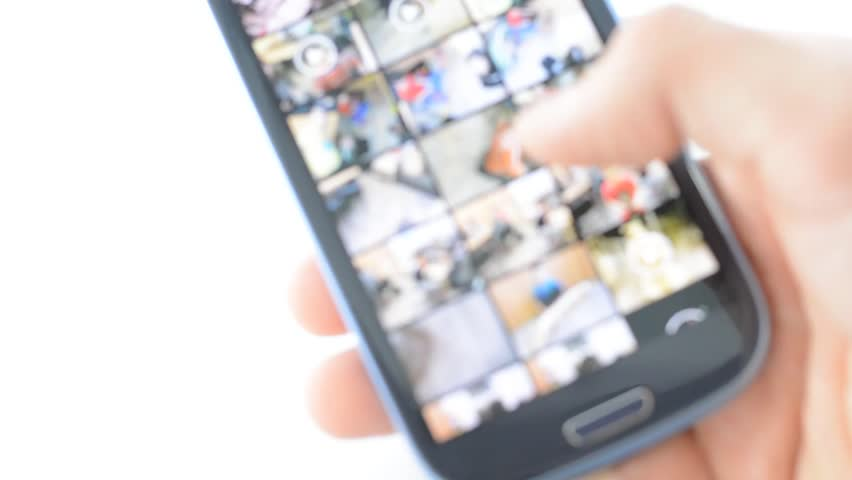 Defocused background. Closeup of young man hands scrolling pictures phone. Isolated on white background. | Shutterstock HD Video #25693067
