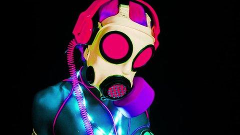 uv fluorescent sexy female gogo dances wearing a gasmask