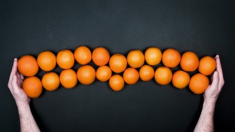 Man Hands Showing And Harvesting Fruits. Stop Motion Animation With Oranges on a Black Background. Top View. 4K.