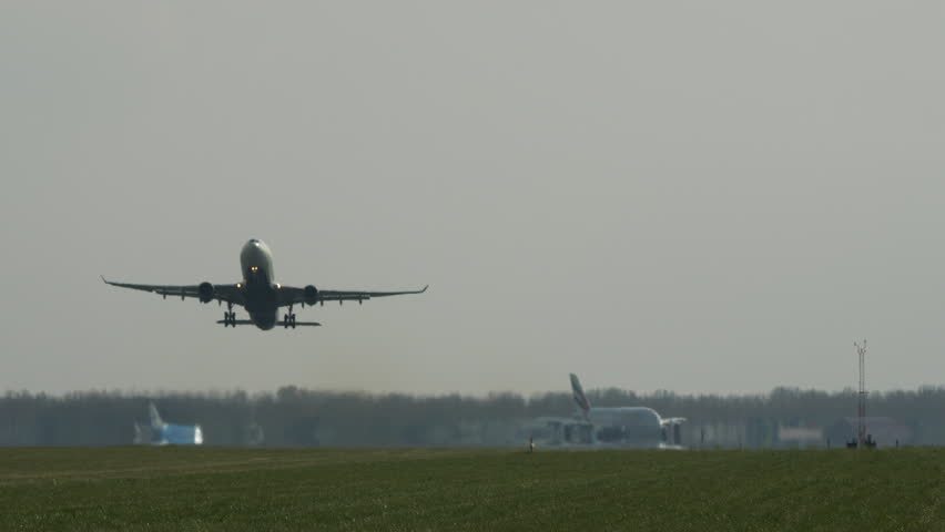 Airplane taking off from runway, long tracking shot. Airplanes lining up behind.