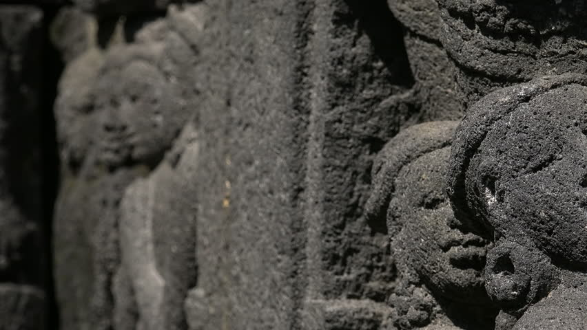 Close-up of wall ornamented with bas-reliefs depicting scene of life in ancient Java and people's faces. Highly detailed stone carving. Borobudur Buddhist temple, Magelang, Indonesia. Panning video.