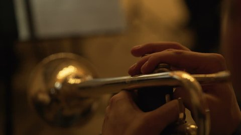 The musician plays the trumpet in the concert hall. musician playing musical instrument. close-up