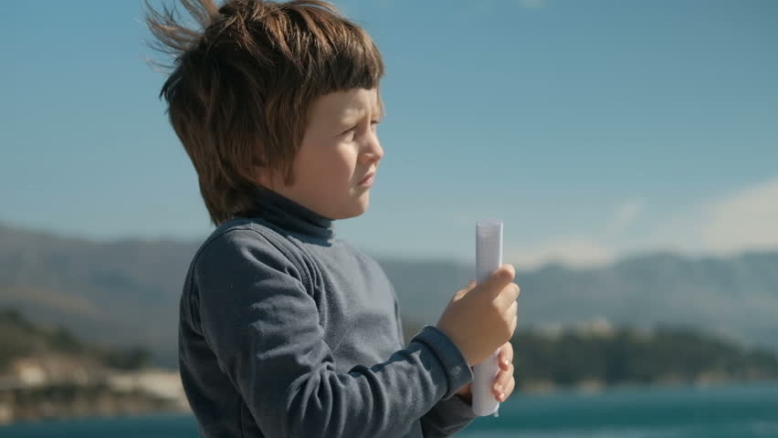 boy folded piece of paper looking into the distance like trumpet to mountains. Slow motion picture of child standing on lake holding hands with paper in cage, like telescope, closed right eye, looks - HD stock footage clip