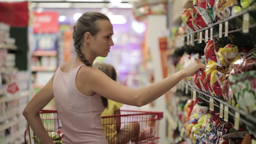 Young mother with little daughter selecting snacks in the sweets section at the supermarket | Shutterstock HD Video #25735397