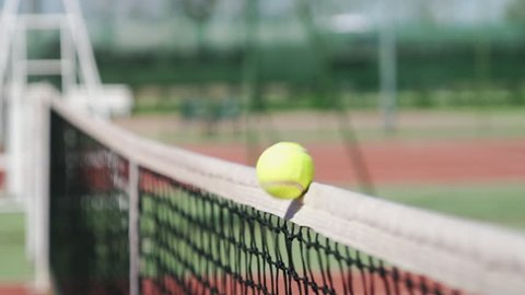 close up of tennis ball hitting the net slow motion