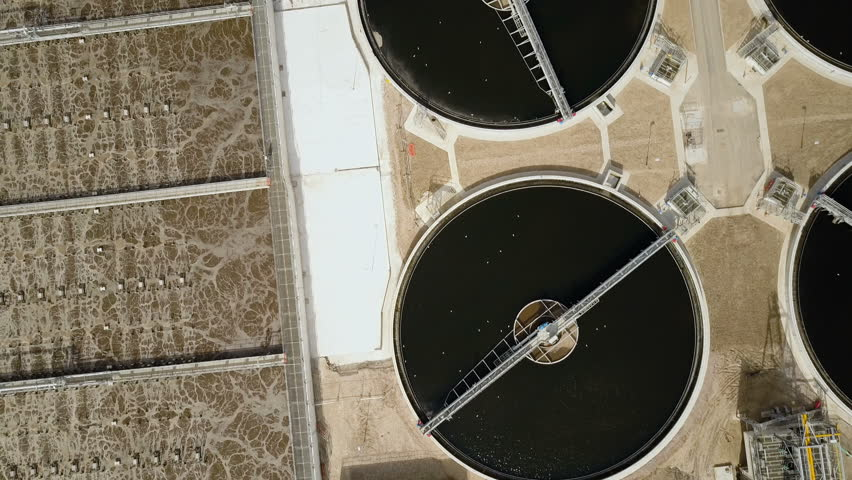Sewage Farm: waste water treatment plant. Forward moving aerial drone video footage looking down onto the various components within a North London sewage farm and water treatment plant.