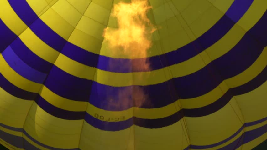 Slowmotion detail shot of an blue and yellow air balloon with the focus on fire.  | Shutterstock HD Video #25779608