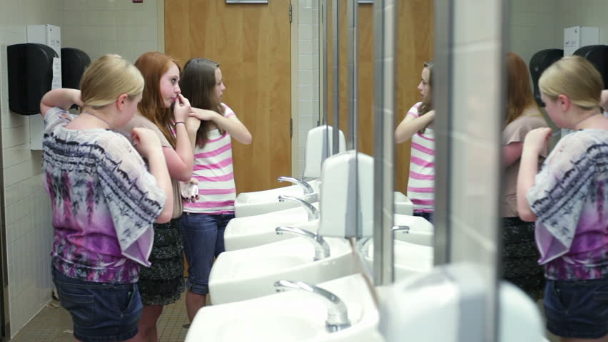 A few girls (students) putting on makeup while talking in a school restroom #2579807