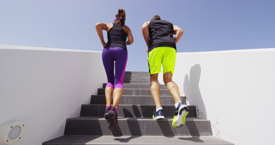 Running on stairs - Runners doing staircase run training outdoors. Woman and man runner athletes climbing stairs in workout run outside. Sport, fitness and healthy lifestyle. RED EPIC SLOW MOTION.