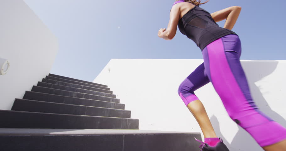 Running stairs - woman runner doing HIIT run up on staircase. Female runner athlete climbing stairs in sport workout run outside. RED EPIC SLOW MOTION.