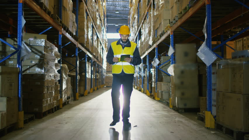 Auditor Wearing Hard Hat with Tablet Computer Counts Merchandise in Warehouse. He Walks Through Rows of Storage Racks with Merchandise.  | Shutterstock HD Video #25809242