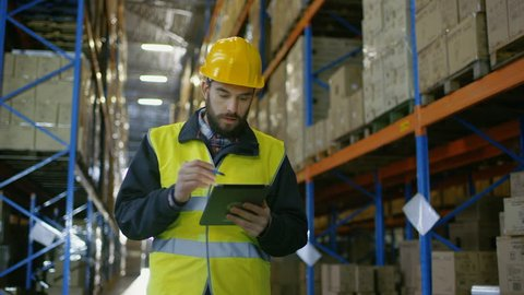 Surveyor Wearing Hard Hat Holds Tablet Computer Counts Merchandise in Warehouse. He Walks Through Rows of Rack Pallets.
