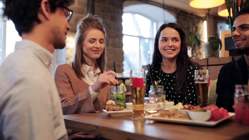 food, drinks, people and holidays concept - happy friends eating, drinking and clinking classes at restaurant #25825397