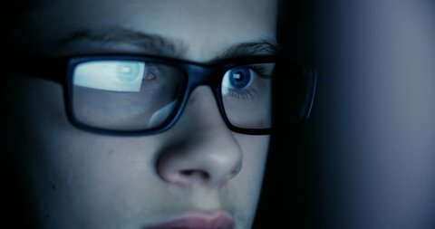 teen boy eyes in the glasses looking at the monitor in a dark room,surfing the Internet, close-up