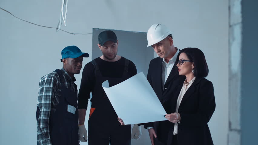 The development group of a project standing and discussing the woman explaining the blueprint to worker when the businessmen and supervisor walking in unfinished room malvernweather Choice Image