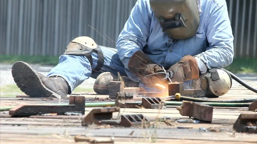 Metal Working Welder At Work Using Water Hose To Cool Job Area