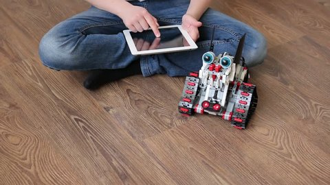 Minsk, Belarus - April 14, 2017: The schoolboy sits on the floor and controls the Dragon-dog robot from a tablet iPad Apple. Lego robot moves and wants to bite. Stem education. E-learning.