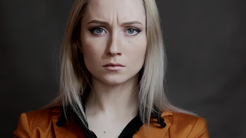 Woman with a strict look on a dark background. In slow motion.