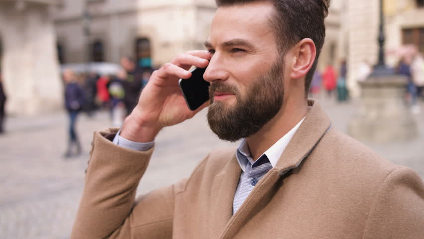 Stylish attractive young man speaking on the phone in the city center | Shutterstock HD Video #25903097