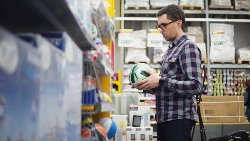 An adult man with black hair, dressed in a plaid shirt, examines the balls that lie on the shelves in the supermarket. A man looks at a volleyball and football ball for outdoor sports. | Shutterstock HD Video #25906295
