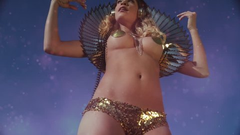amazing sexy woman dances outside in a sparkling gold costume. good burning man or festival rave concept.