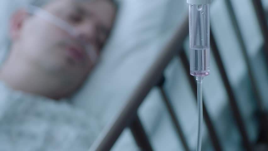A sick middle aged man with an IV drip recovering in a hospital bed, slow motion, 4K   Shutterstock HD Video #25907837