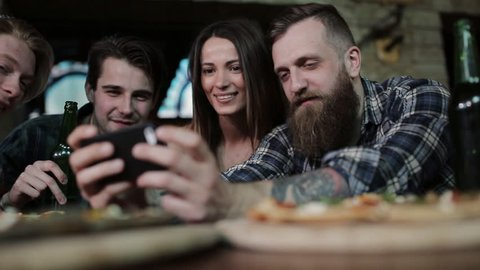 A stylish guy with a beard at a table in a cafe shows his friends photos on the phone