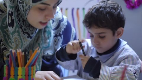 BEIRUT, LEBANON - 2016: Muslim veiled kindregarten teacher helps a child in coloring. Women make up 22.6% (2011) of the total labour force in Lebanon