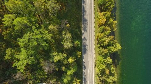 Car rides on the road between trees near the lake. green Forest. Sunny summer spring day. Green water. Mountains. Top view of cars. Aerial view top down 4k