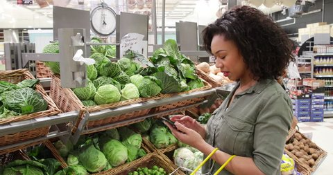 Woman in grocery store using smart phone shopping list
