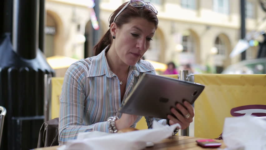 Young woman using tablet computer in cafe - HD stock footage clip