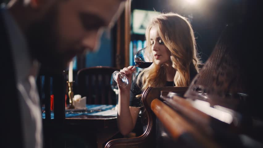Gorgeous young woman in a classic black dress drinking red wine and seductively looking at the young bearded musician playing the vintage piano. Romantic atmosphere, perfect date. Couple goals.