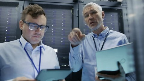 Footage Shot from Rack Server Cabinet. Two IT Technicians Use Laptop and Tablet Computer Work on Hardware and Software. Shot on RED EPIC-W 8K Helium Cinema Camera.