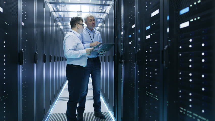Two IT Engineers Standing in Working Data Center. They Use Laptop and Tablet Computer while Standing Beside Open Server Rack Cabinet. Shot on RED EPIC-W 8K Helium Cinema Camera.
