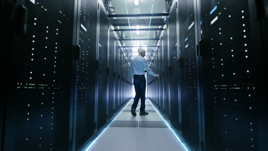 Server Engineer in Data Center Walks Through Sliding Doors and Opens Server Rack Cabinet. Shot on RED EPIC-W 8K Helium Cinema Camera.