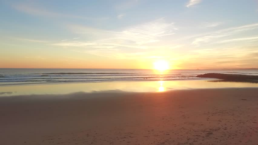 Aerial video in motion of sunset in the Atlantic Ocean in Costa da Caparica, Lisbon, Portugal