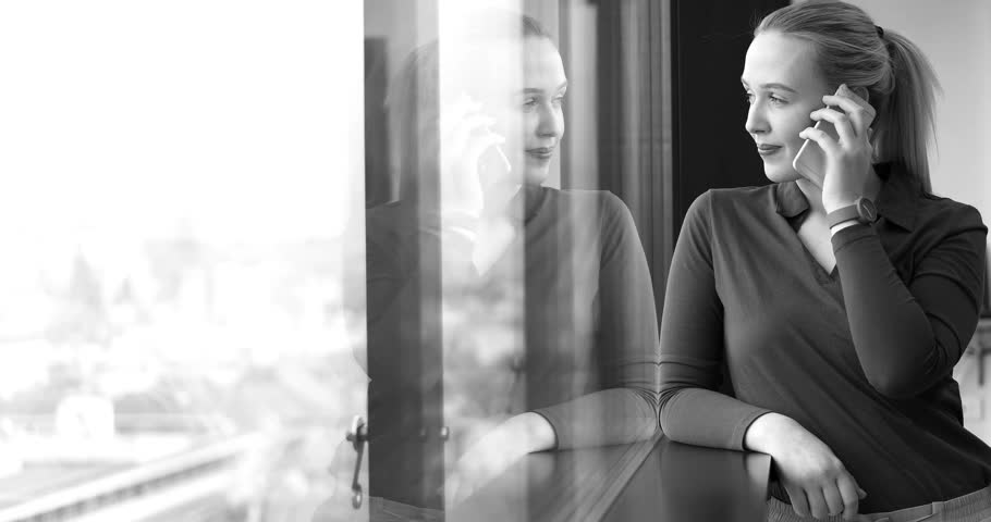Elegant Woman Using Mobile Phone by window in office building | Shutterstock HD Video #26012357