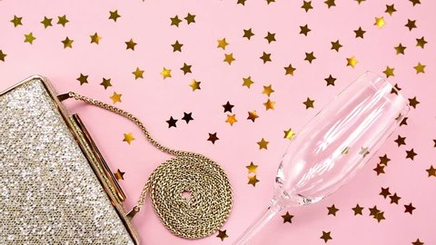 Festive evening golden clutch and champagne glass with star sprinkles shining on pink. Holiday and celebration background. Luxury accessories and party concept.