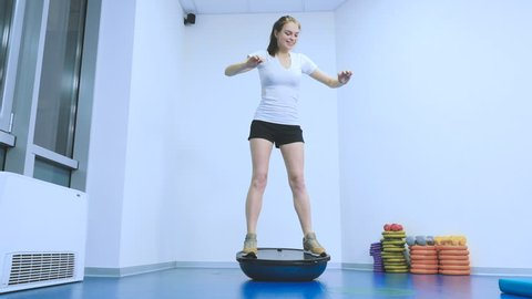 Young smiling girl keep the balance on the simulatur bosu in the gym
