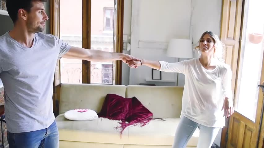 Beautiful and vivacious young couple dancing in living room of apartment. | Shutterstock HD Video #26042297