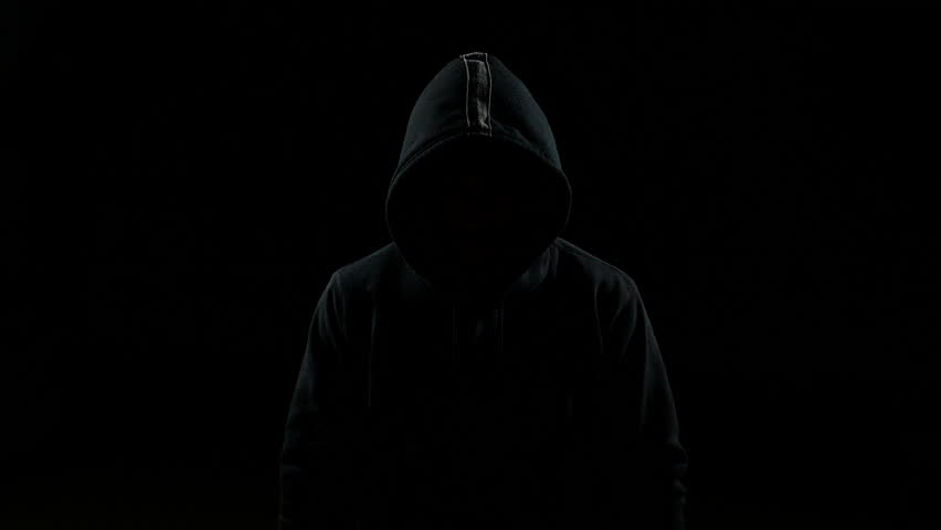 Portrait of invisible man with a hood nodding his head indoor on black background