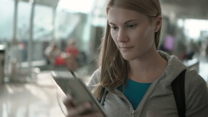 Relaxed woman using travolator in airport terminal. Using her smartphone, listening to the music | Shutterstock HD Video #26064257