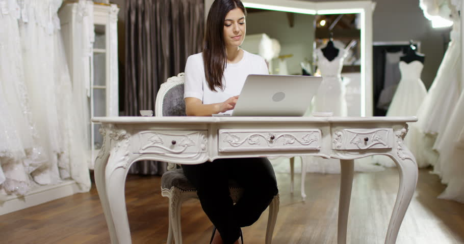 4K Young woman working on laptop in bridal wear boutique, with elegant wedding gowns on display in background. Slow motion. | Shutterstock HD Video #26070008