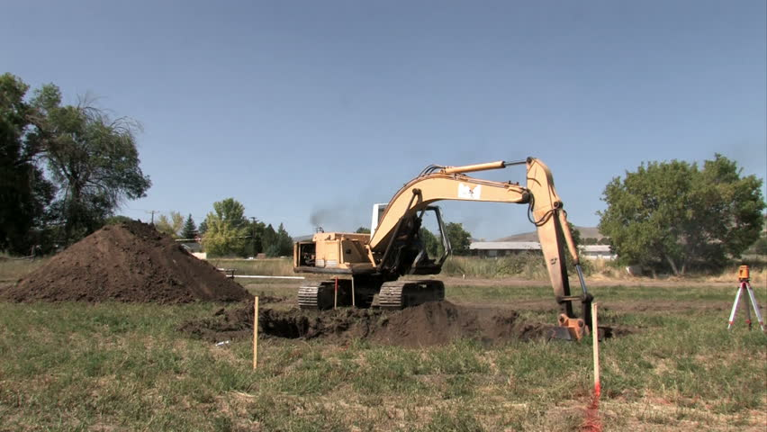 SANPETE COUNTY, UT - SEPT 16: backhoe excavator machine digging a basement for a new house or home. Located in the middle of a farm field. Construction slowdown but not stop.